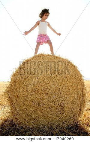 Girl playing over the round wheat dried bale outdoor summer