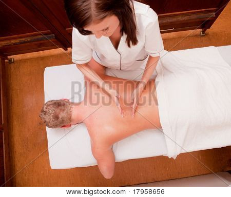 A man receiving a percussive back massage at an old style spa