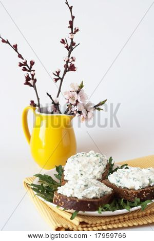Cheese snack on rye bread and a bouquet