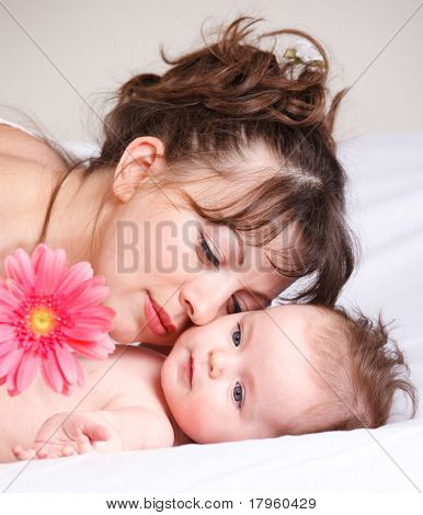 Gorgeous baby looking at the pink flower, mother lying beside