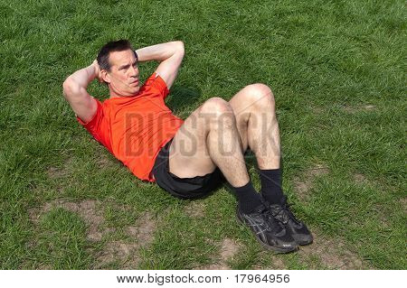 Man Exercising doing Situps on the Grass