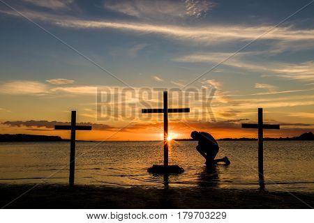 Man kneeling ion prayer at three crosses at sunset