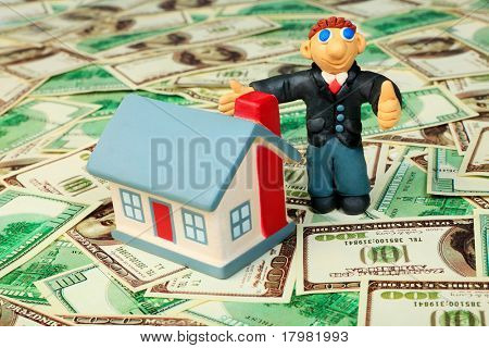 Shot of a plasticine businessman with a house over money background.