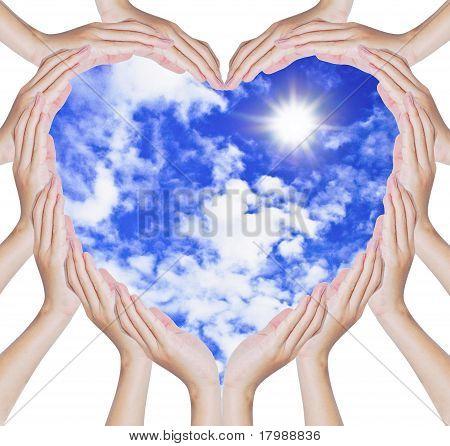 Manos hacen en forma de corazón en el cielo azul