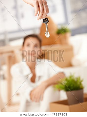 Young woman sitting on floor, man hanging keys of new house in foreground.?
