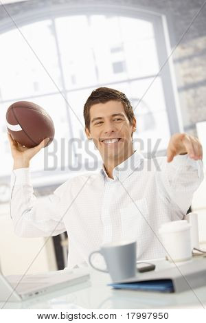 Cheerful businessman sitting in office throwing football at colleague, pointing, laughing.?