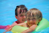 picture of swimming pool family  - A sister and brother swimming in a pool - JPG