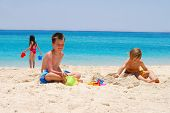 picture of beach holiday  - Children playing on the beach building sand castles and carrying water - JPG