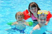 picture of swimming pool family  - Three happy children floating in a outdoor pool - JPG