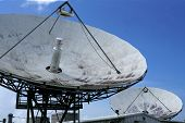 Parabolic satellite dish space technology receiver over blue sky