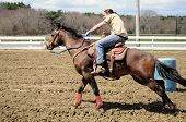 stock photo of barrel racing  - A young man turns around a barrel and races to the finish line - JPG