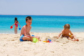 pic of beach holiday  - Children playing on the beach building sand castles and carrying water - JPG