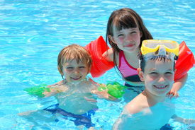 stock photo of swimming pool family  - Three happy children floating in a outdoor pool - JPG