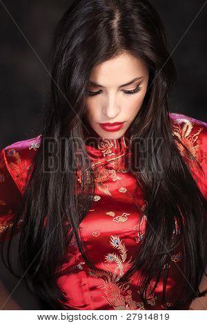 Mujer en Cheongsam rojo sobre fondo oscuro