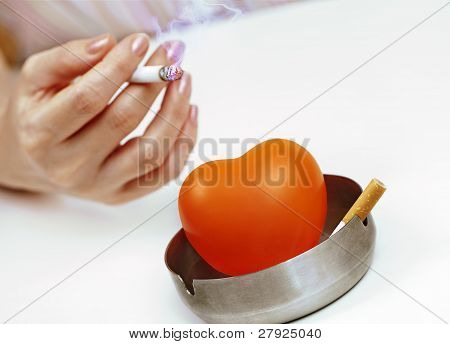 Orange Heart In  Ashtray And A Woman's Hand With A Cigarette.