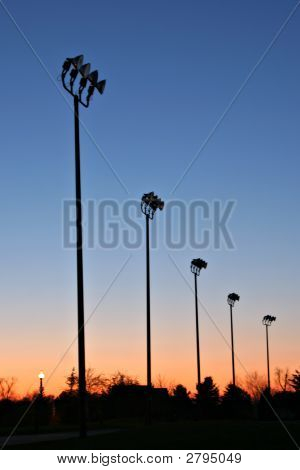 Light Poles Silhouette At Dawn