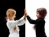 Hand Shake And High Five. The Portrait Of Two Happy Holding Hands Girls On A White And Black Studio  poster