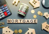 Wooden Houses, A Calculator, Keys, Coins And Blocks With The Word Mortgage. Buying A Home In Debt. P poster