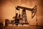 image of nonrenewable  - Oil pump jack dark Red filtered image - JPG