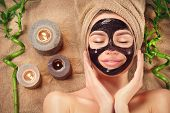 Beautiful woman with black purifying black mask on her face. Beauty model girl with black facial pee poster