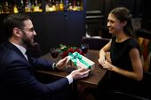 Happy young man passing giftbox to pretty girl to make her valentine surprise poster