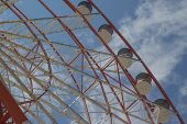Ferris Wheel On A Bright Sunny Day. Brightly Colored Ferris Wheel Against The Cloudy Sky. Fragment A poster