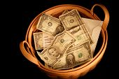 image of tithe  - A basket full of money with very dramatic lighting - JPG