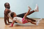 Handsome Black Young Father And His Cute Little Daughter Are Doing Reverce Plank With Leg Raise On T poster