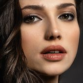 Beautiful woman with  brown eyes. Fashion model with a smokey makeup. Closeup portrait of a pretty w poster