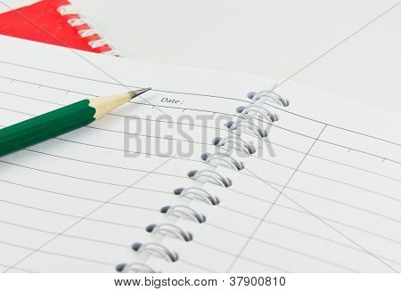 Pencil On The Open Blank Notepad Shows Blank Date With Isolated White Background