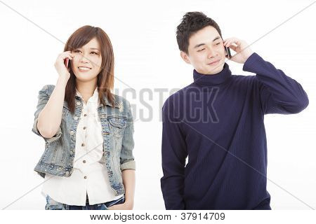 Young Couple Talking On Mobile Phone Isolated On White