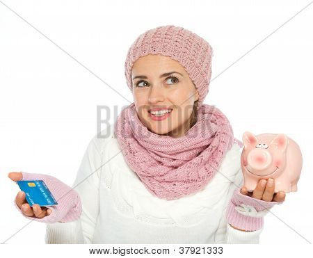 Confused Woman In Knit Winter Clothing Holding Credit Card And P