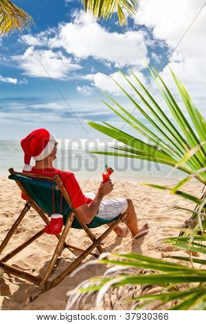 Man In Santa's Hat With Cocktail Sitting On Chair On A Beach