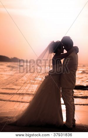 couples of groom and bride  romance scene on sea beach with sun set background