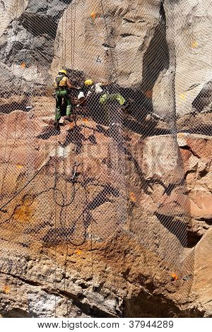 Workers tension a metallic net on rocks