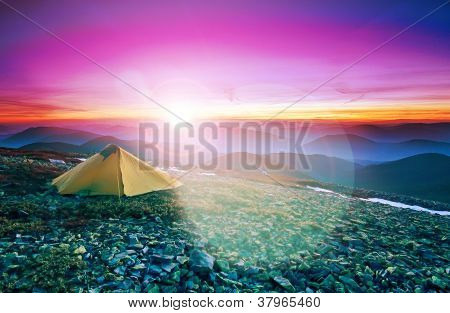 Tourist Tent In The Rocky Mountains And Flaring Sun