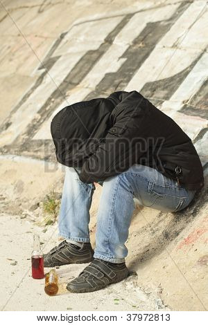 Boy sleeping under a bridge with two drink bottles near
