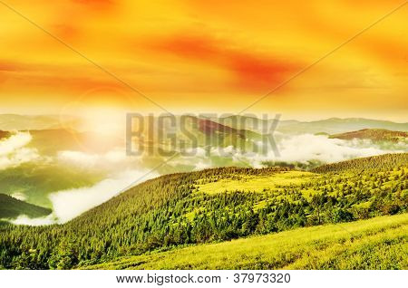 Flaring Sun, Golden Sky And Cloudy Carpathian Mountains