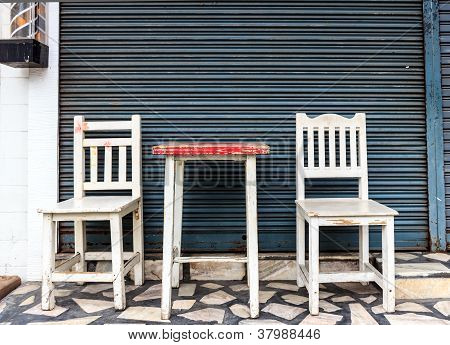 Set Of Wooden Chairs In Front Of Steel Shutter Door