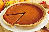 picture of pumpkin pie  - Whole pumpkin pie with a slice cut out
