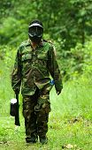 stock photo of gun shot wound  - Picture of man playing paintball in the jungle - JPG