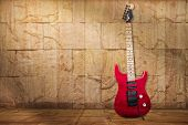 foto of stratocaster  - A red electric guitar lean against a sandstone wall - JPG