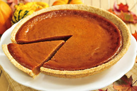 stock photo of pumpkin pie  - Whole pumpkin pie with a slice cut out  - JPG