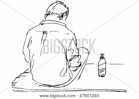 fellow sits on a table with the bottle of beer