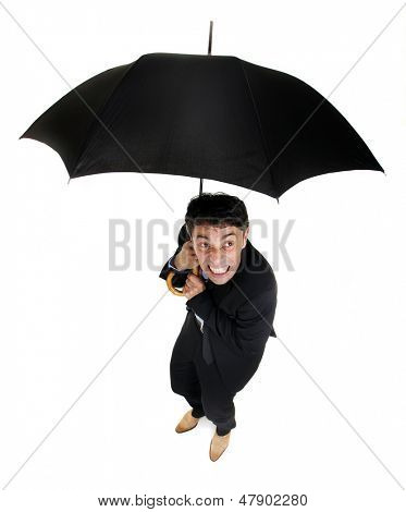 Humorous high angle full length portrait of a squeamish business cowering under an umbrella as he looks up at the inclement rainy weather around him