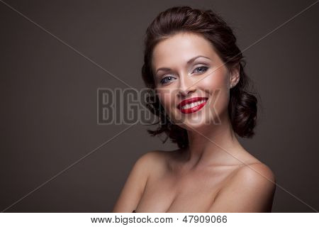 Face of a beautiful young brunette woman with bright lipstick and curly hair