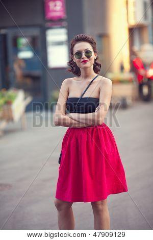 Summer street portrait of a beautiful young Caucasian girl