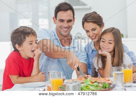 Man cutting a pizza for his family for the dinner