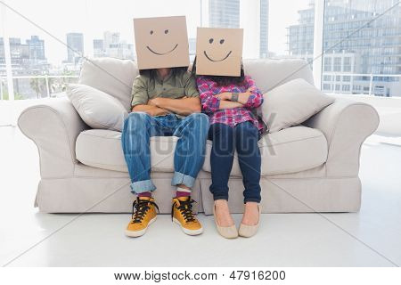 Silly employees with arms folded wearing boxes on their heads with smiley faces on a couch