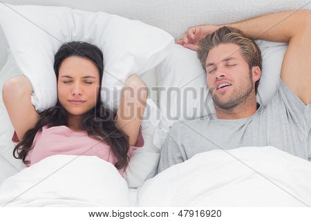 Woman annoyed by the snoring of her partner in her bed